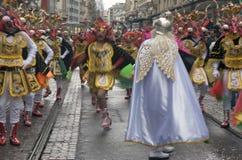 Os dançarinos trajados em uma rua desfilam - guerreiros do demónio Fotografia de Stock