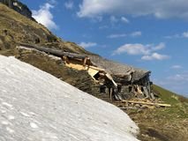Os danos às explorações agrícolas da montanha causadas por avalanchas nevados no verschneite Lawinen do durch de Schäden da regi imagens de stock royalty free