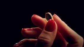 Os dedos da mão mostram comprimidos com a droga das cápsulas da ômega 3 video estoque