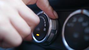 Os dedos da mulher que ajustam o botão do condicionador de ar do carro video estoque