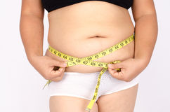 Os dedos da mulher que medem sua gordura da barriga Foto de Stock