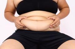Os dedos da mulher que medem sua gordura da barriga Imagem de Stock