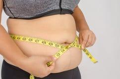 Os dedos da mulher que medem sua gordura da barriga Fotografia de Stock