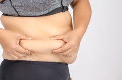 Os dedos da mulher que medem sua gordura da barriga Foto de Stock Royalty Free