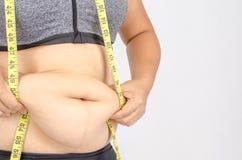 Os dedos da mulher que medem sua gordura da barriga Imagens de Stock