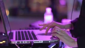 Os dedos do ` s do DJ jogam no portátil video estoque