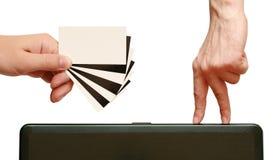 Os dedos estão indo contrastar o cartão em han Imagem de Stock