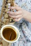 Os dedos estão prontos para jogar as chaves do piano e os botões do saxofone foto de stock