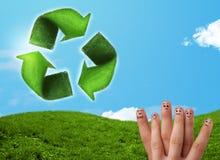 Os dedos felizes do smiley que olham a folha verde reciclam o sinal Fotografia de Stock