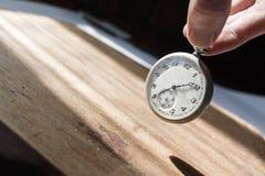 Os dedos guardam o relógio de bolso do vintage com vidro rachado foto de stock royalty free