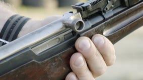 Os dedos masculinos carregam o rifle do cartucho um por um vídeos de arquivo