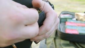 Os dedos masculinos carregam o rifle do cartucho um por um filme