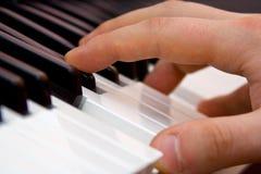 Os dedos na chave do piano Imagem de Stock