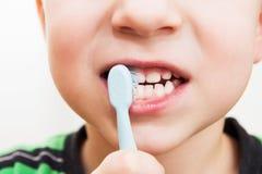 Os dentes da criança com uma escova de dentes Fotografia de Stock Royalty Free