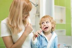Os dentes de escovadela bonitos do filho da mãe e da criança aproximam o espelho no banheiro fotos de stock royalty free