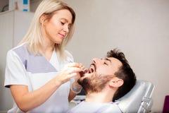 Os dentes do paciente masculino de exame do dentista fêmea novo em uma clínica dental imagem de stock