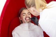 Os dentes que claream o dentista da recep??o da menina do procedimento para os dentes que clarea o doutor aplicam a droga aos den imagem de stock