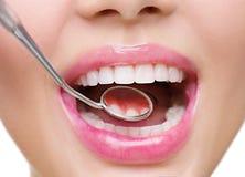 Os dentes saudáveis de mulher branca e um espelho de boca do dentista imagem de stock