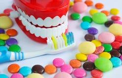 Os dentes zombam acima com escova de dentes e os doces coloridos Imagem de Stock