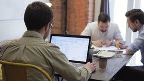 Os desenhos de projeto colaboradores das imagens do trabalho no portátil da reunião, discutem video estoque