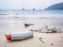 Os desperdícios do lixo no plástico da praia engarrafam a poluição ambiental do lixo imagem de stock