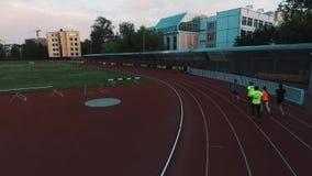 Os desportistas da opinião do zangão agrupam movimentar-se na trilha do estádio do esporte na noite vídeos de arquivo
