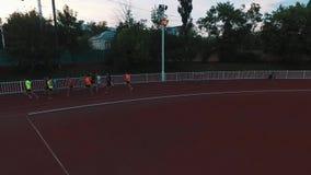 Os desportistas da opinião do zangão agrupam o corredor na trilha do estádio do esporte na noite vídeos de arquivo