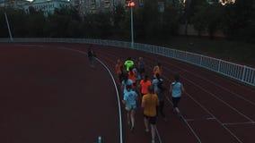 Os desportistas da vista aérea agrupam movimentar-se na trilha do estádio do esporte na noite filme