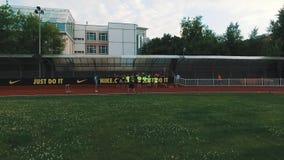 Os desportistas deitam o grupo que está na fileira em trajeto running do estádio vídeos de arquivo