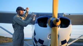 Os detalhes de um avião estão obtendo verificados e limpados por um especialista masculino do avião filme