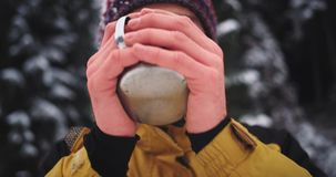 Os detalhes do retrato de mãos congeladas que guardam um copo do ferro, homem do turista obtêm mornos no meio da montanha nevado video estoque