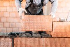Os detalhes, fecham-se acima do pedreiro da construção que constrói paredes interiores fotos de stock