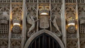 Os detalhes interiores arquitetónicos de pedra cinzelaram a brasão acima da entrada principal dos reis Faculdade Capela fotos de stock