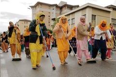 Os devotos sikh varrem a estrada com os pés descalços no festival 2013 de Baisakhi em Bríxia Fotos de Stock