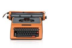 Os Di cortam alaranjado e a máquina de escrever preta no fundo branco, copia o spac Fotos de Stock