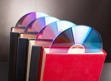 Os discos do CD são colam para fora do livro vermelho Imagens de Stock
