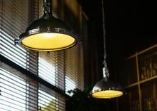 Os dispositivos bondes à moda que penduram do teto, brilham a luz suave amarela Nas janelas das cortinas, no fundo, dri alcoólico fotografia de stock