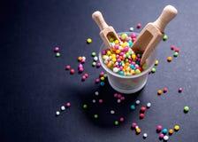 Os doces coloridos, açúcar perolizam com a colher de madeira no fundo preto Imagem de Stock