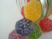 Os doces coloridos derramaram um frasco de vidro fotos de stock royalty free