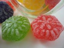 Os doces coloridos derramaram um frasco de vidro fotos de stock