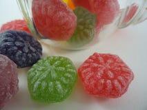 Os doces coloridos derramaram um frasco de vidro fotografia de stock royalty free