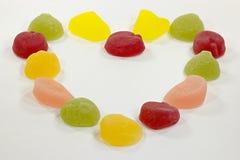 Os doces coloridos do fruto arranjaram na forma do coração Imagem de Stock Royalty Free