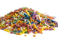 Os doces coloridos polvilham isolado no fundo branco fotos de stock royalty free