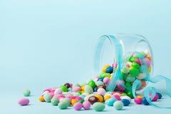 Os doces coloridos são dispersados no fundo azul Presentes para o aniversário ou a Páscoa feliz Fotografia de Stock Royalty Free