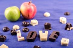 Os doces de chocolate brancos e pretos, o coração, as figuras, duas maçãs e a palavra amam foto de stock