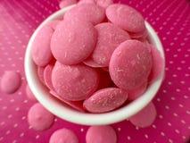 Os doces de chocolate cor-de-rosa derretem no fundo cor-de-rosa dos às bolinhas Fotos de Stock