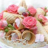 Os doces, os marshmallows, a pastilha, os cones do waffle e as rosas cor-de-rosa naturais são decorados sob a forma de um ramalhe fotografia de stock royalty free
