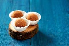 Os doces redondos da lentilha do vegetariano no pó de cacau na placa do carvalho copiam Imagens de Stock Royalty Free