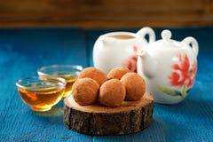 Os doces redondos no pó de cacau no carvalho embarcam com chá e bule Fotografia de Stock Royalty Free