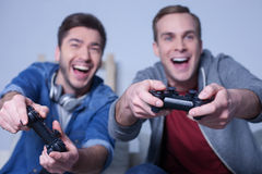 Os dois amigos bonitos estão divertindo a estação do jogo foto de stock royalty free